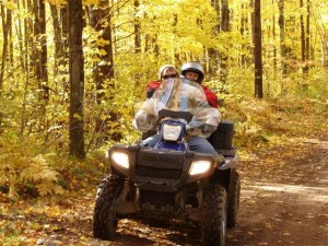 A four-wheeler with 2 passengers driving through yellow woods