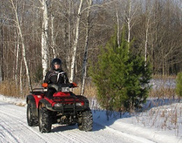 Red four-wheeler zips down a snowy road